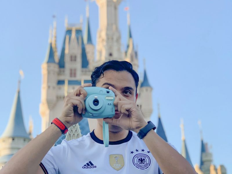 Photo of man taking a photo at a less crowded day at Disney which was found using the Disney Crowd Calendar