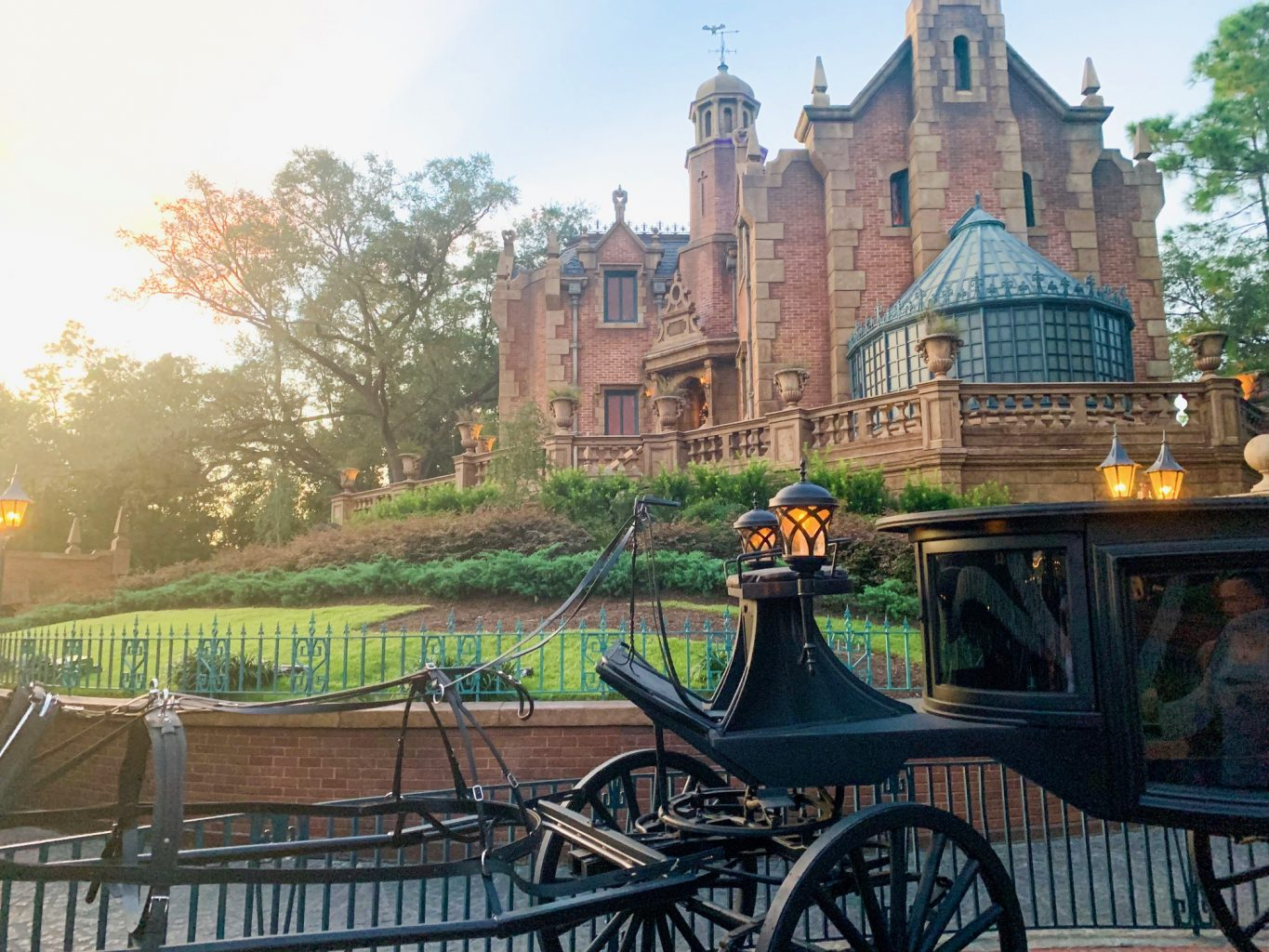 The outside of Haunted Mansion, one of the best Magic Kingdom rides, with a black carriage out front.