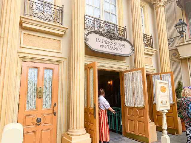 France Pavilion entry to Impressions de France with door open and cast member inviting in guests