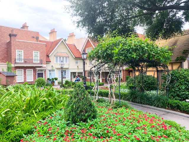 Countries in Epcot view of United Kingdom Pavilion with green gardens, trees, and front of shops