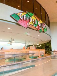 exterior of Garden Grill restaurant with colorful sign and empty booth seating