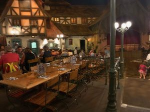 long wooden tables with German inspired houses in the background