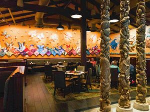 intricately carved totem poles in front of bright wall background Disney restaurants