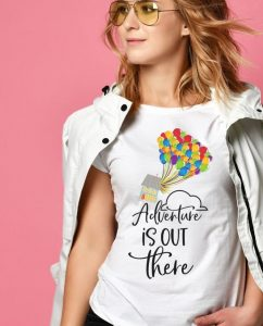 girl in front of pink background wearing Disney's Up-inspired shirt