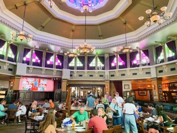 Disney Springs Restaurants Raglan Road interior main dining room with stained glass and chandeliers with people at tables