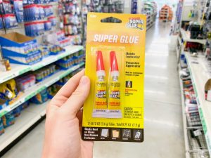 hand holding two-pack of super glue Dollar Tree Disney