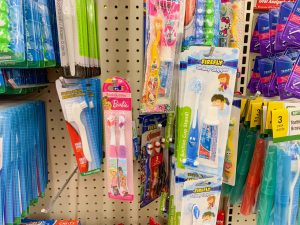 shelf full of Disney-themed toothbrushes for kids