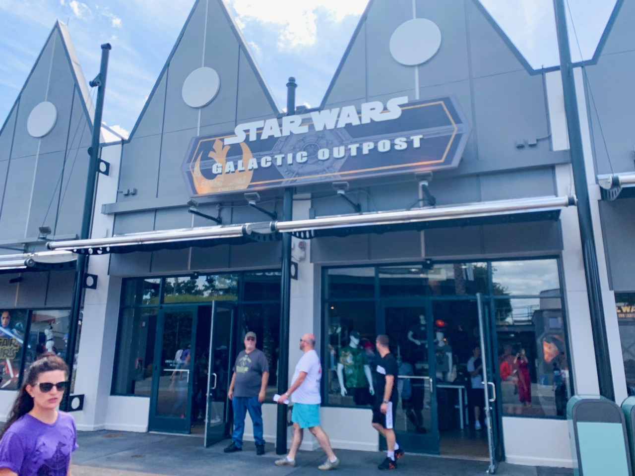 "Storefront of the Star Wars Outpost which is a silver building with two large triangles on top with a sign that says ""Star Wars Galactic Outpost"" and people walking in and out of the store"