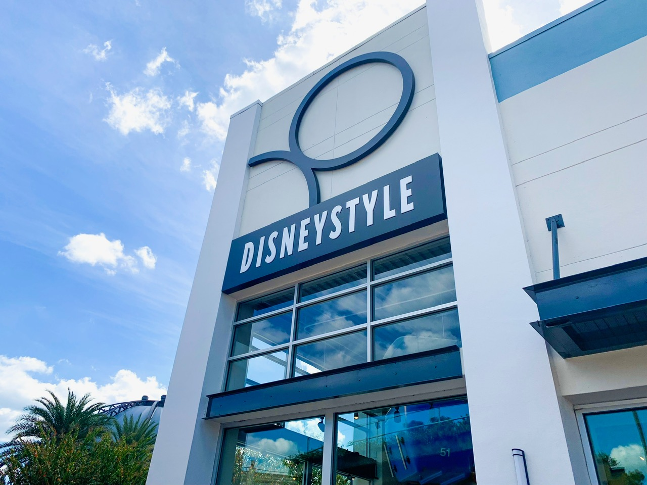 Storefront of DisneyStyle at Disney Springs. The storefront is an off white color with large windows and a dark blue sign with white, all capital DisneyStyle letters. There is a blue sky and clouds in the background.