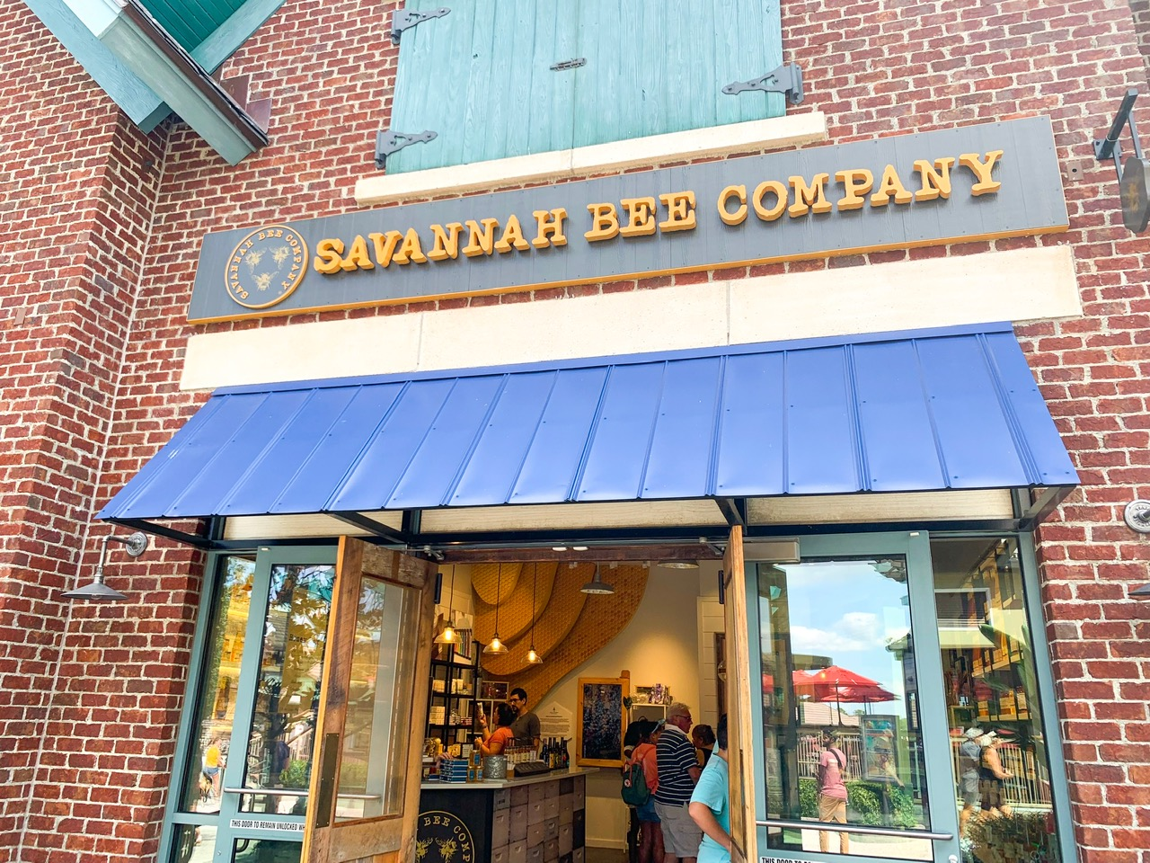 Storefront of the Savannah Bee Company - a brick building with a blue awning and yellow letters on a grey background