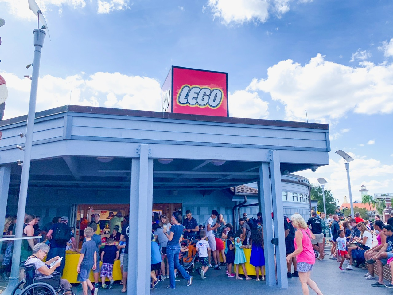 "A crowd of people outside of the Lego store with white pillars and a red sign with white ""lego"" letters on top on a blue sky and cloudy day"