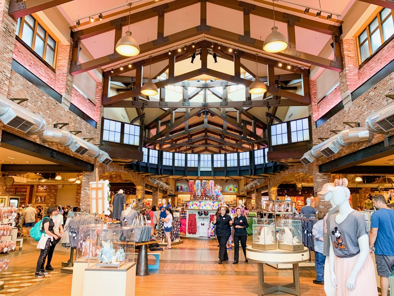 Inside of large Disney Springs Store with a brick interior, lots of windows and open space, with several people walking around shopping