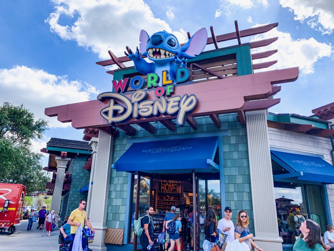 "Storefront of World of Disney store at Disney Springs. It is a large grey store, with lots of people outside walking around, and has a blue awning. The store name is on a maroon background with multicolored letters for ""World of"" and then the Disney font in a soft yellow."