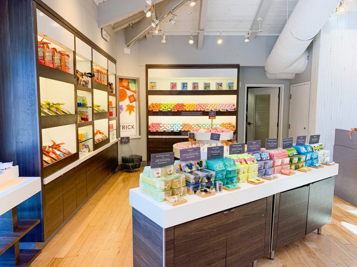 Multi colored soaps displayed on a table in the foreground, with other bath products displayed on shelves in the background