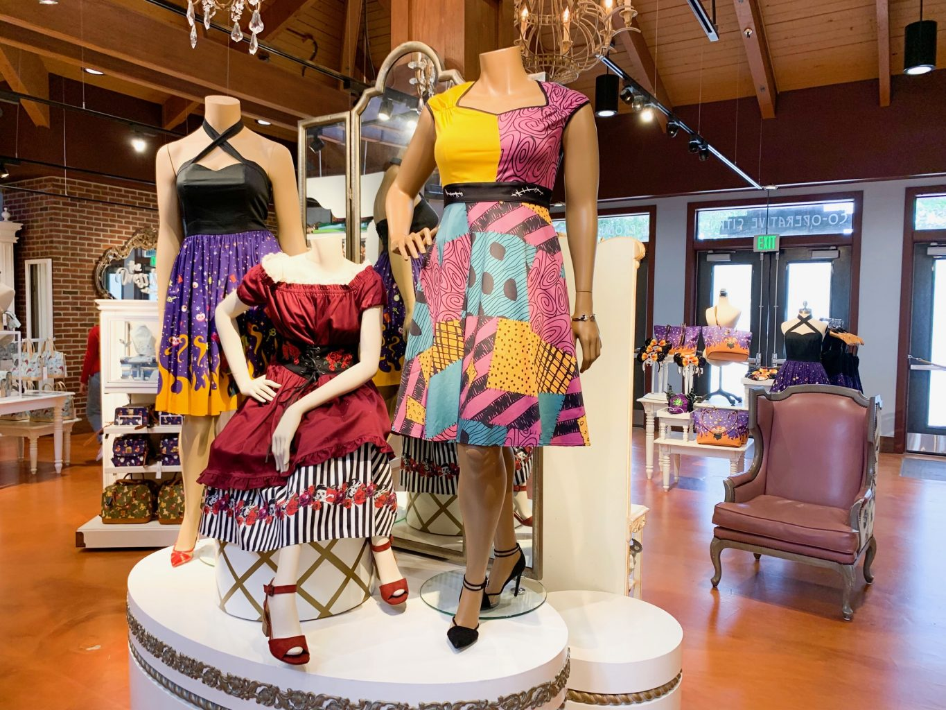 Set of three dresses on display inside the Marketplace Co Op store at Disney Springs. The dress on the far right has a color block yellow and pink top and a pink, yellow, and blue skirt with polka dots in some of the multi colored squares. The middle dress is dark red with a black and white striped under skirt peeking out from the bottom. The far left dress has a black criss-crossed halter top with a purple skirt with a flame pattern on the bottom.