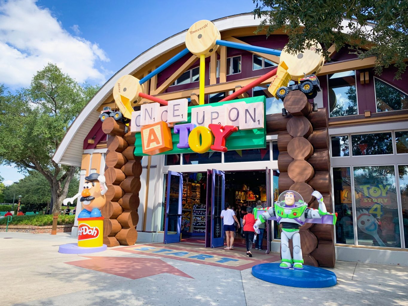 "Storefront of Once Upon a Toy at Disney Springs. The storefront is decorated like a log cabin, with Mr. Potato head sitting on a container of Play-Doh on the left side and Buzz Lightyear on the right side. The words ""Once Upon"" are in scrabble tiles, the ""A"" looks like a toy block, and ""Toy"" is made up of toy alphabets in blue, yellow, and red respectively."