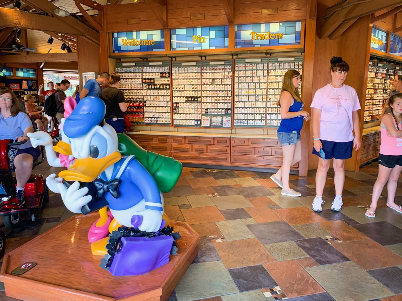 Inside of the Pin Traders store at Disney Springs with Donald Duck in the foreground and two people shopping in the background
