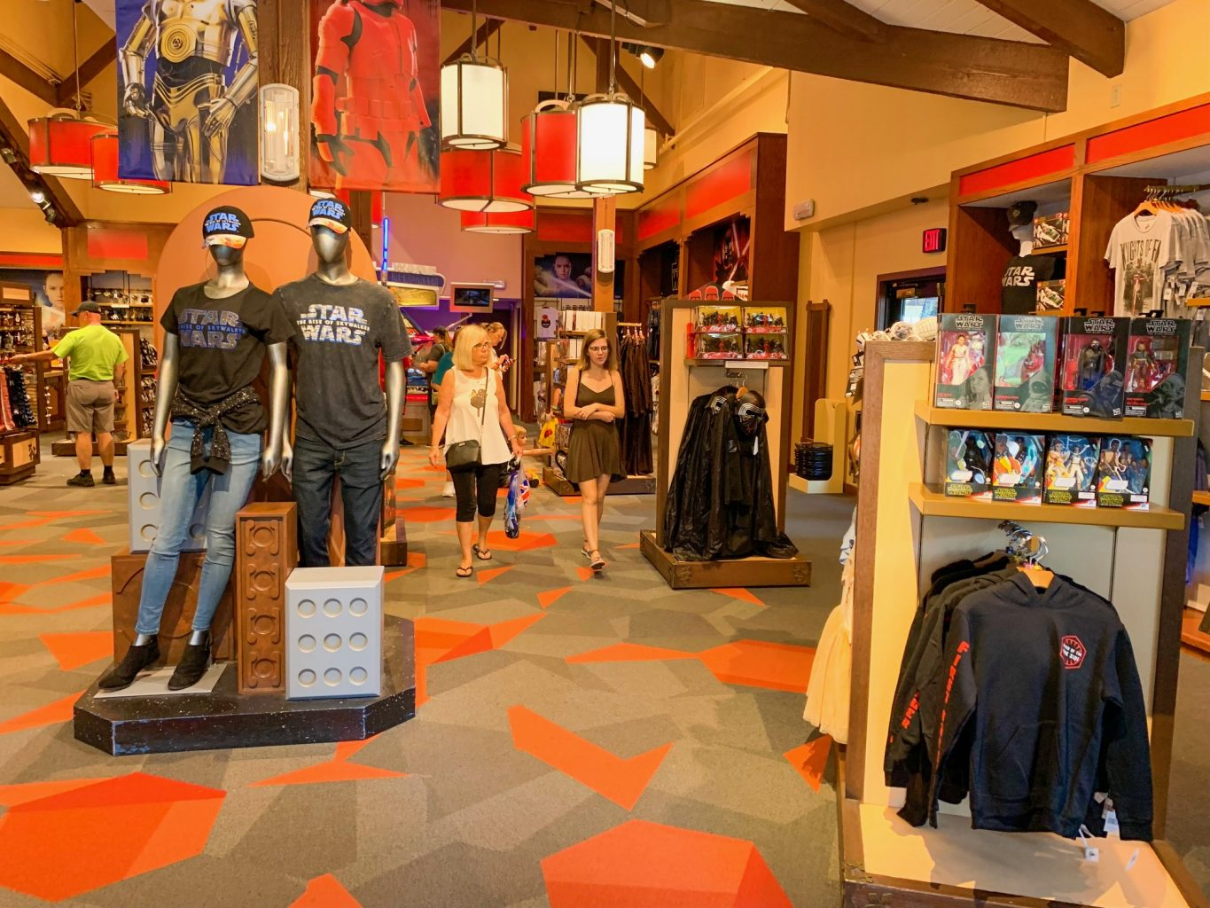 Inside of the Star Wars Trading Post at Disney Springs with large Star Wars artwork on the back wall, tall ceilings, a display in the front right corner with Star Wars clothing, and two mannequins in the center left wearing black Star Wars t shirts, jeans, and black caps with the Star Wars logo.