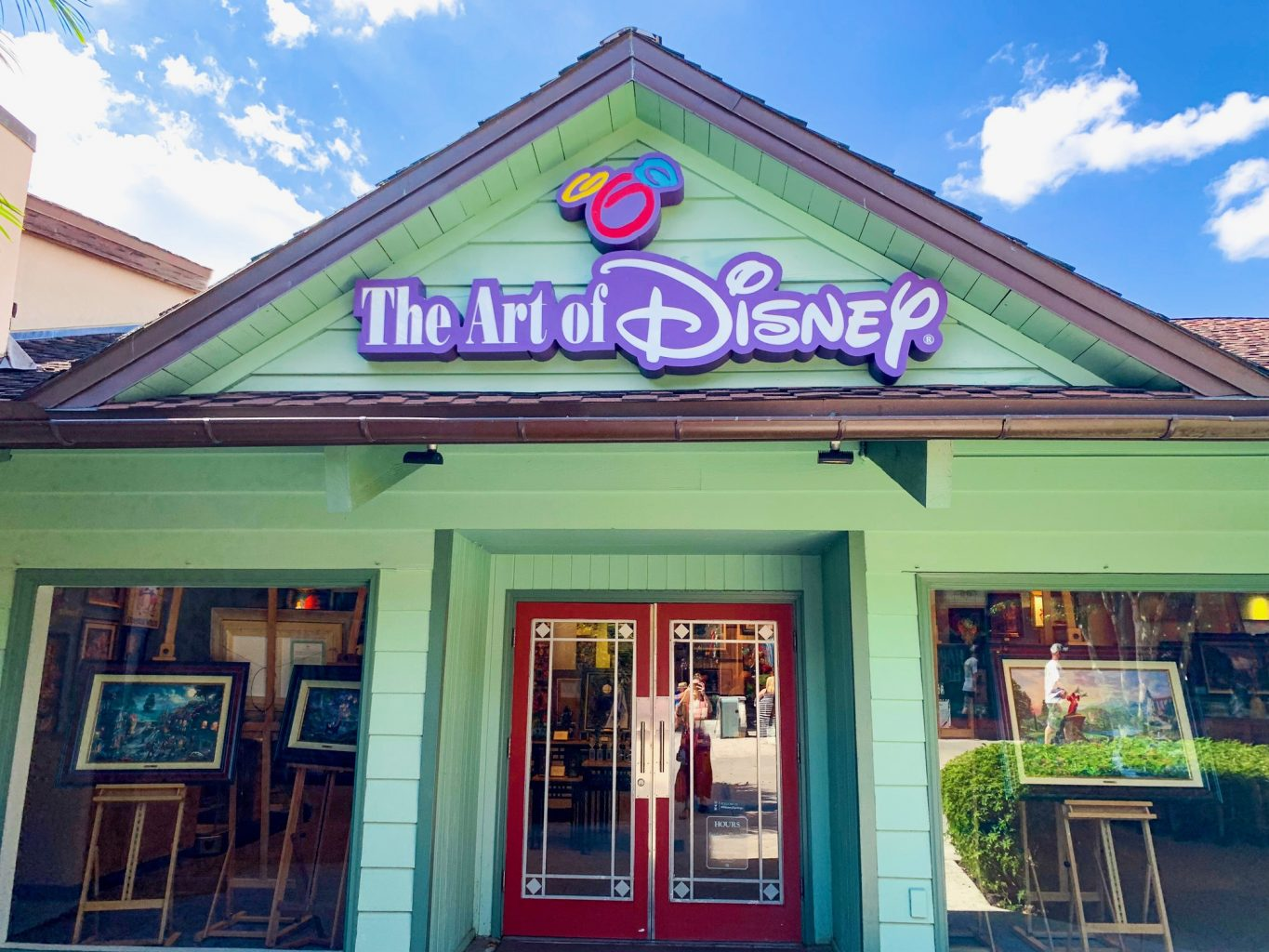 Storefront of Disney Springs Store The Art of Disney which is a green building with white letters outlined in Purple