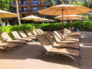 empty pool chairs with umbrellas
