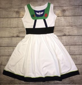 white dress with black trim and green and red buttons