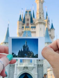 woman holding a polaroid picture of Cinderella's Castle in front of Cinderella's castle