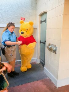 Winnie the Pooh and cast member by secret door