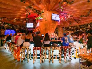 red-lit bar area with people sitting on animal-themed chairs