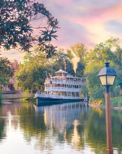 three tiered riverboat cruising on a river at sunset