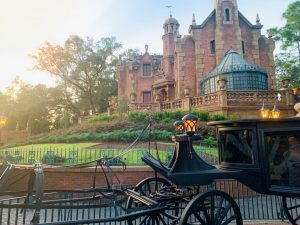 exterior of the Haunted Mansion with a black carriage in front with no horse
