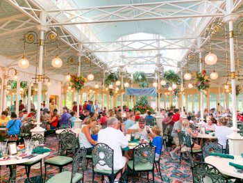 greenhouse-like dining area filled with people Magic Kingdom restaurants