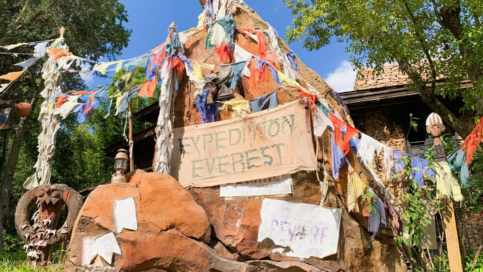 battered expedition everest sign surrounded by torn cloth pieces