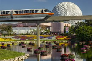 Disney tram running by Epcot ball over flower-decorated area Epcot Flower and Garden Festival