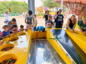 children lining up their lego cars along a bright yellow race track