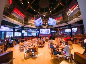 dining area with wooden chairs and a dozen TVs showing sports games