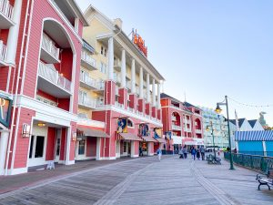 red, yellow, and light blue buildings lining a wooden promenade Disney Boardwalk