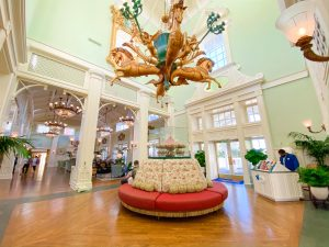 vintage style interior with golden horse chandelier and rounded couch Disney transportation