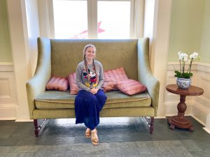 woman in Mickey sweatshirt sitting on vintage-style olive couch