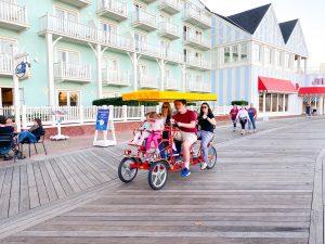 family cruising along the Disney Boardwalk in a surrey bike