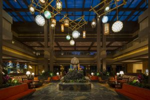 island inspired lobby with tiki holding leis