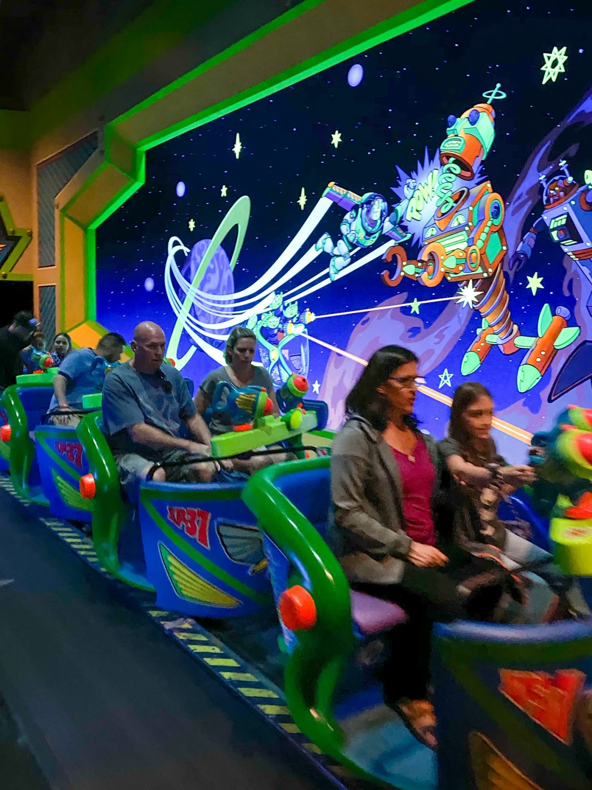 people on Buzz Lightyear ride getting ready to go