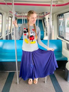 girl in blue skirt and Mickey sweater in empty monorail car