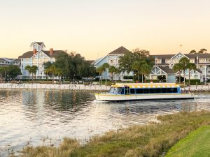 boat departing from light blue hotel at sunset Disney transportation