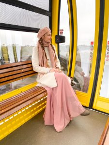 girl in cozy pink outfit in yellow Skyliner gondola