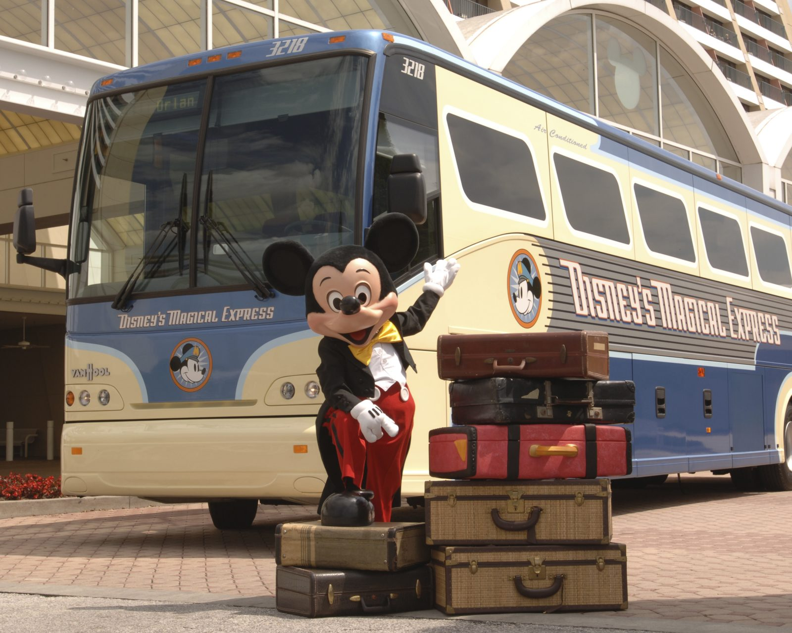 photo of Mickey Mouse and luggage in front of the Magical Express; tipping at Disney