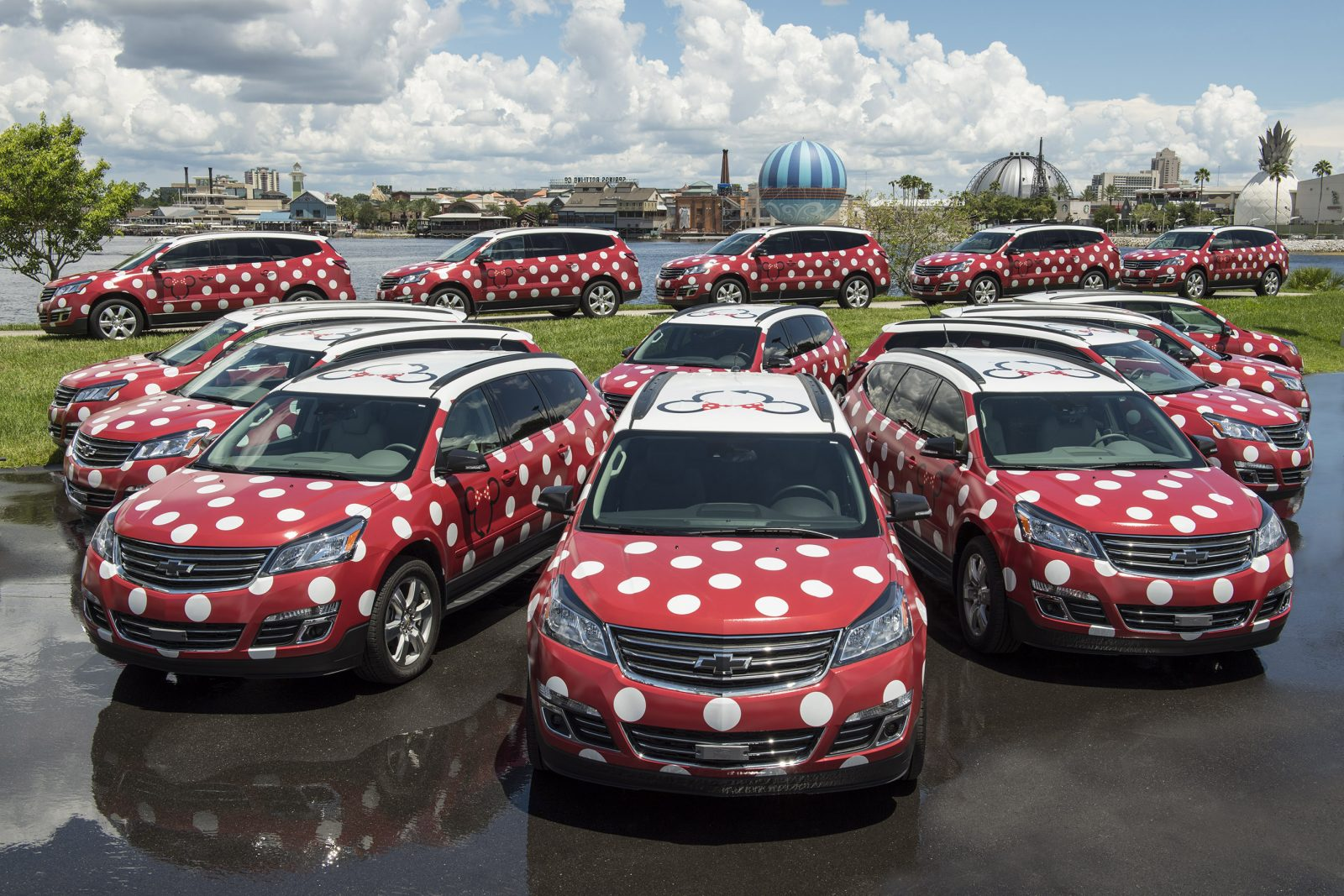 photo of a fleet of red vans with white Minnie spots; tipping at Disney
