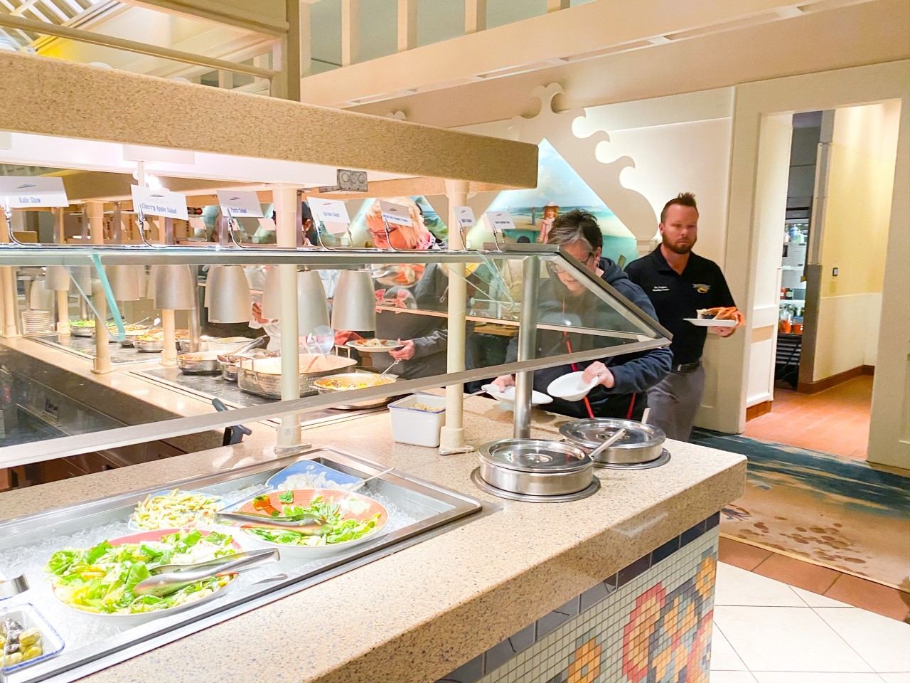photo of people serving themselves at a buffet restaurant, tipping at Disney