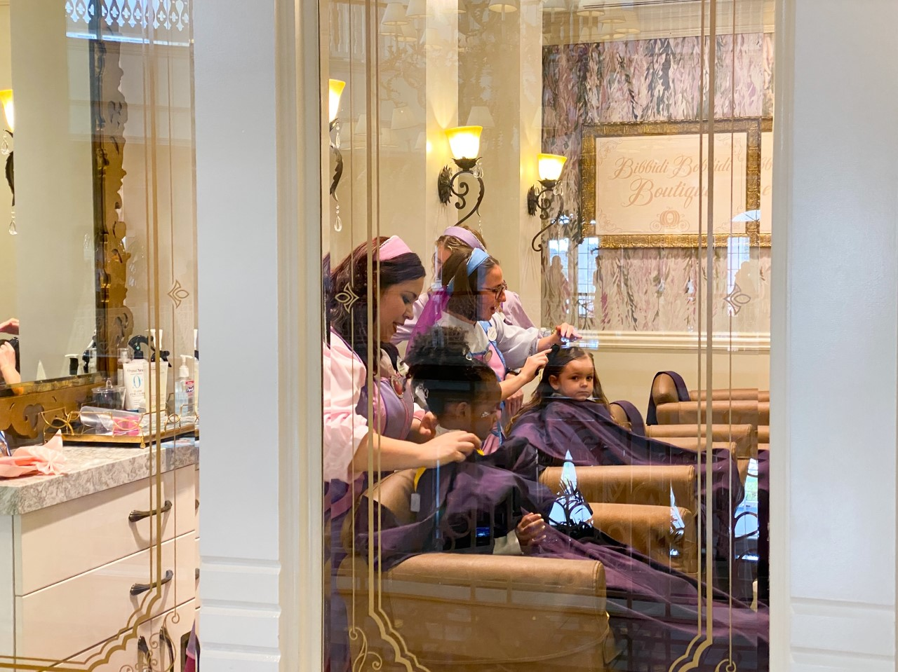 photo of children having their hair dressed at Bibbidi Bobbidi boutique by Fairy Godmothers in training; tipping at Disney